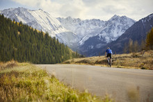 Rear View Of Man Riding Bicycle On Country Road Against Snowcapped Mountains