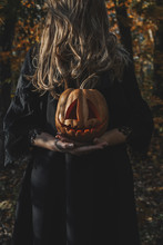 Woman Covering Her Face With Hair And Holding Jack O Lantern