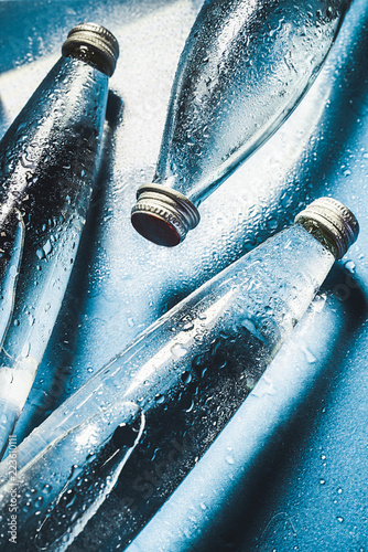 A glass bottle of water on blue background splashes drops of water on top Wallpaper Mural
