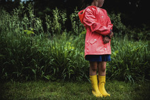 Girl In Raincoat Standing In Park