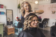 Cheerful hairdresser spraying beauty product on customer's wavy hair in salon