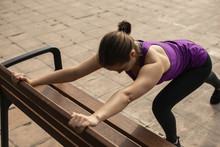 Young Woman Stretching On Wooden Bench In Park