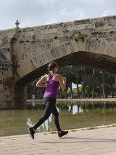 Rear View Of Woman Jogging On Footpath By Pond In Park