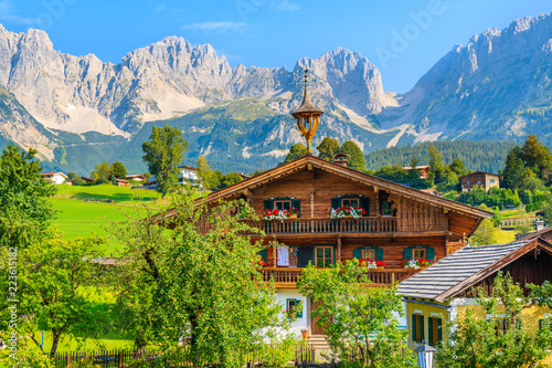 Vászonkép  Typical wooden alpine house against Alps mountains background on green meadow in