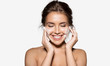 Portrait of cheerful laughing woman applying foam for washing on her face. Lovely brunette with attractive appearance. Skincare spa relax concept. Isolated on grey background