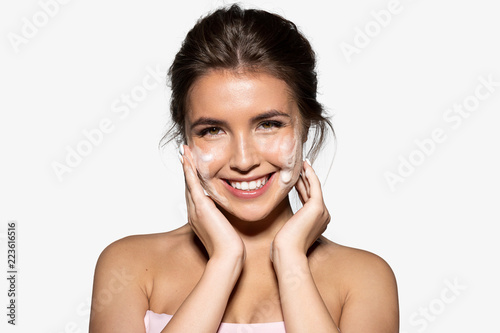 Obraz Portrait of joyful young woman applying white foam for washing. Cheerful brunette with perfect clean skin looking at camera with gladness. Skincare spa relax concept. Isolated on grey background - fototapety do salonu