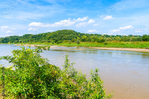 View of Vistula river and green hills near Cracow city on sunny summer day, Poland