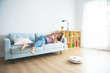 Cleaning the house's robotic vacuum cleaner, when women based on sofas play mobile phones