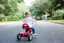 Young Child Toddler On Red Tricycle On A Neighborhood Street Looking At Camera