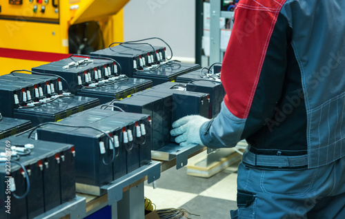 Obraz A gloved worker connects the batteries to the factory - fototapety do salonu
