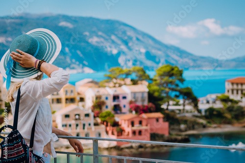 Tourist woman wearing blue sunhat and white clothes enjoying view of colorful tranquil village Assos on sunny day фототапет