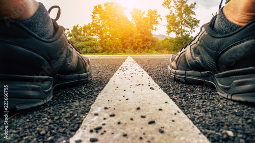 running shoes, athlete running sport feet on asphalt road with straight white line and sunset background, fitness and healthy lifestyle concept (selective focus)