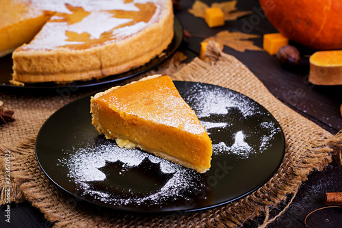 Photo  American homemade pumpkin pie with cinnamon and nutmeg, pumpkin seeds and autumn leaves on a wooden table