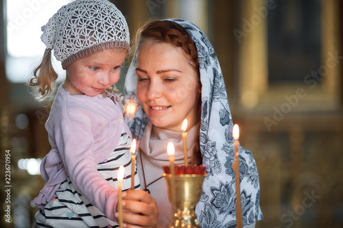 Fotografia Russian beautiful woman in a scarf and with red hair holding a little girl and lights a candle in front of an icon in the Russian Orthodox Church