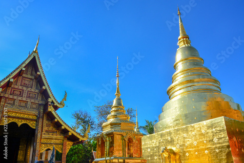 Fotobehang Temple golden Buddhist temple, shiny golden pagoda and wooden church at Wat Pra Sing with blue sky background, Chiang-mai province northern of Thailand