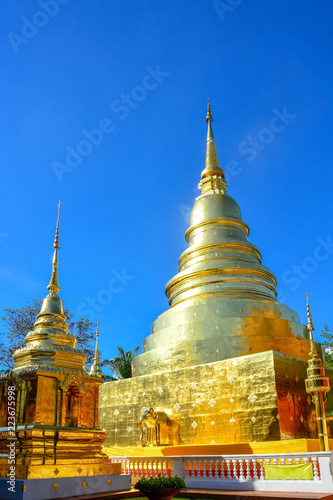 Staande foto Temple golden Buddhist temple, shiny golden pagoda at Wat Pra Sing with blue sky background, Chiang-mai province northern of Thailand