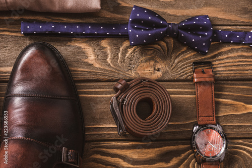 Fotografia  top view of leather male shoes, bow tie, belt and wristwatch arranged on wooden