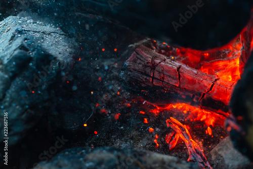 Fotografiet  Smoldered logs burned in vivid fire close up