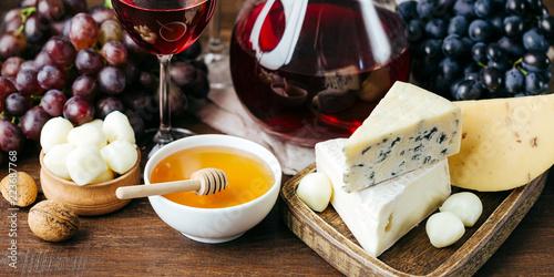 Ser i wino, karafki i okulary, drewniane tło, przekąska, winogrona, długi baner