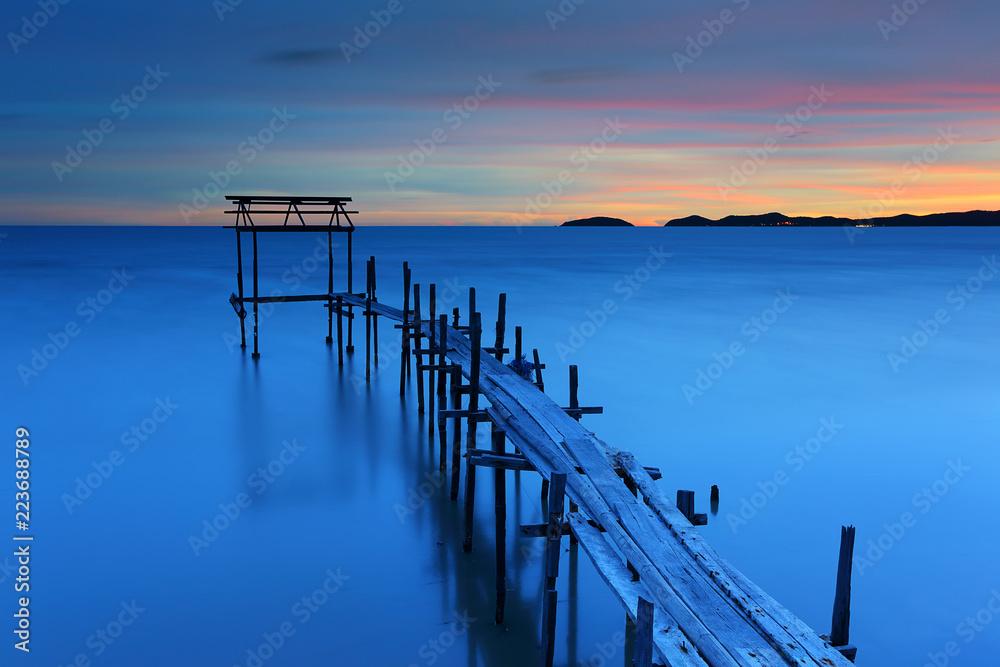 Beautiful sunset at old wooden bridge on sea coast