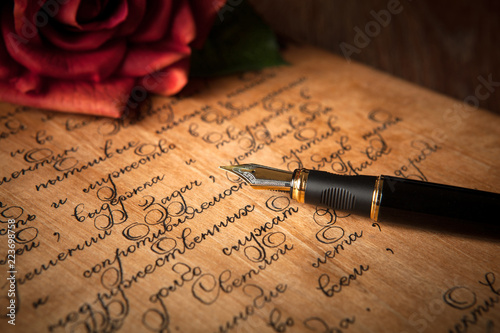 fountain pen on letter with text and red rose on a table