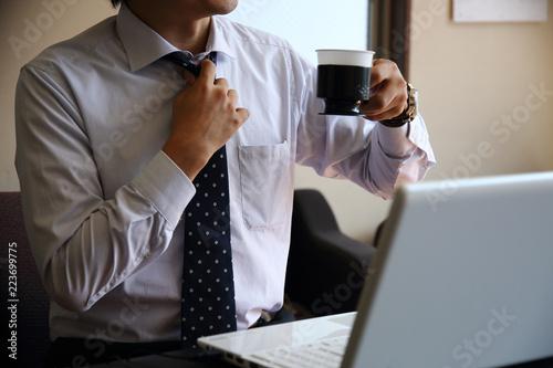 Photo  パソコンの前でコーヒーを飲むビジネスマン