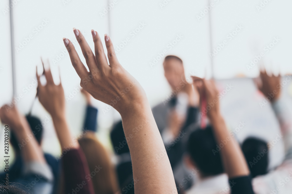 Fototapety, obrazy: Audience raising hands up while businessman is speaking in training at the office.