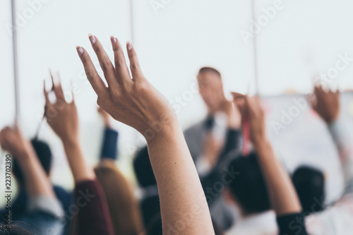 Audience raising hands up while businessman is speaking in training at the office Wallpaper Mural