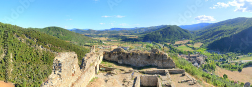 A landscape of cultivated fields, dense forest and mountains as seen from the ruins of the abandoned castle in the rural medieval town of Boltaña, in the Spanish Aragonese Pyrenees