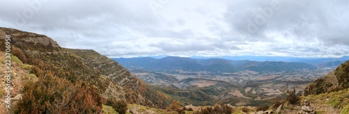Fotomural Blue cloudy sky and typical mountains and hills covered with forest met in autum
