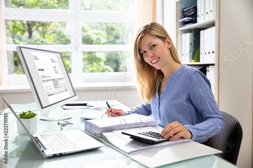Fotomural  Young Businesswoman Calculating Bill In Office