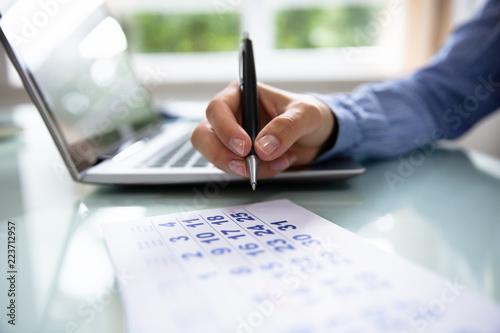 Obraz Businesswoman Marking Date On Calendar - fototapety do salonu