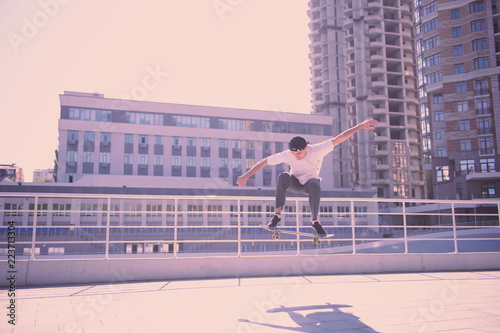 In the air. Concentrated brunette man wearing sporty clothes while doing extreme tricks