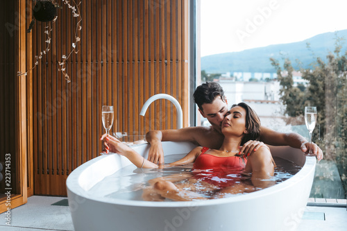 Tableau sur Toile Couple enjoying a bath with champagne