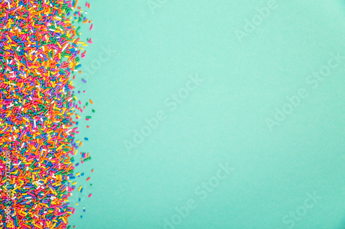 Fotomural Colorful sprinkles on edge of green background