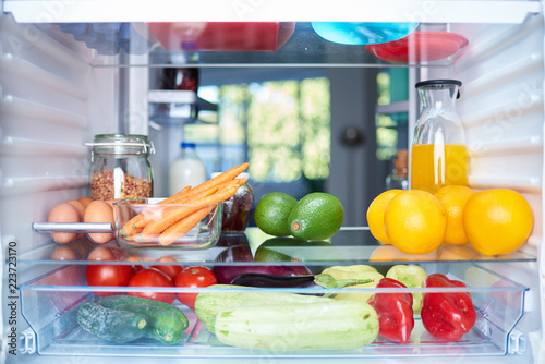 Obraz Opened fridge from the inside full of vegetables, fruits and other groceries. - fototapety do salonu