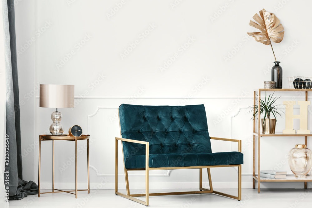 Fototapeta Dark green sofa with golden frame by a white wall with molding in an elegant living room interior with expensive decor