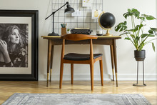 Mid-century Modern Chair With Leather Seat By A Desk With An Industrial Lamp And A Retro Typewriter In A White Home Office Interior
