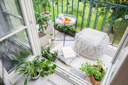 Fotografie, Obraz Top view of a balcony with plants, pouf a table with breakfast