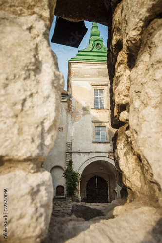 Papiers peints Con. Antique View of the entrance tower through the hole in the wall. Castle in the Lviv region. Olesko