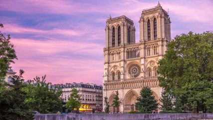 Front view of Notre Dame De Paris cathedral day to night timelapse after sunset.