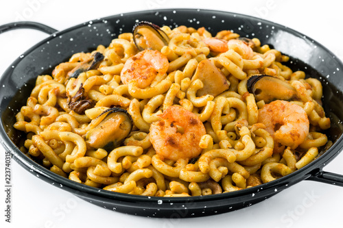 Traditional Spanish fideua. Noodle paella isolated on white background.