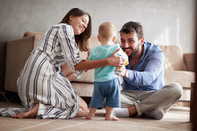 Happy Family - Mother And Father Playing With A Baby At Home.