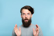 Leinwanddruck Bild omg unbelievable shock amazement. dumbfounded man with open mouth. portrait of a young bearded guy on blue background. emotion facial expression and reaction concept.