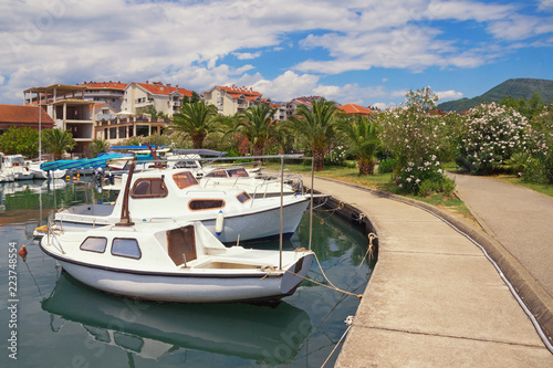Picturesque Mediterranean landscape. Embankment of seaside town, with view of fishing boats in harbor and green park. Montenegro, Tivat city, Marina Kalimanj