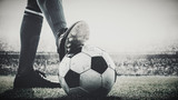 Fototapeta Sport - feet of soccer player tread on soccer ball for kick-off in the stadium black and white