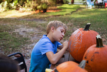A Boy Making A Jack-o-lantern From A Pumpkin.