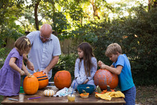 A Father And His Children Making Jack-o-lanterns Out Of Pumpkins.