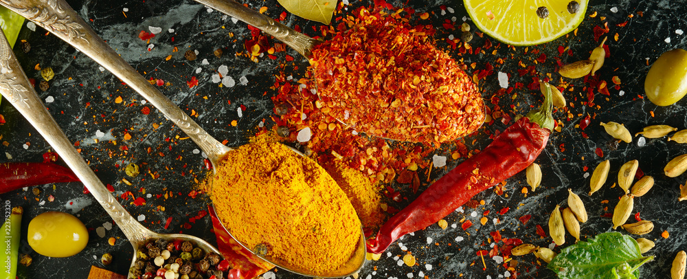 Fototapeta Variety of spices and herbs on kitchen table. Wide photo.
