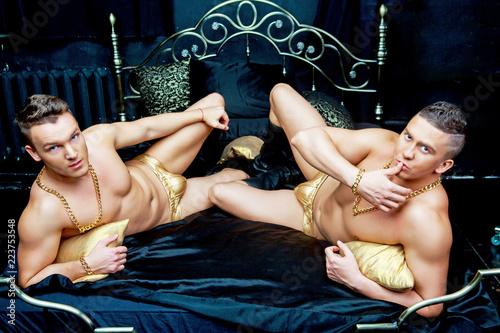 Vászonkép  muscular men   in bed with black linen